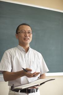 黒板の前で授業をする先生の写真素材 [FYI03928734]