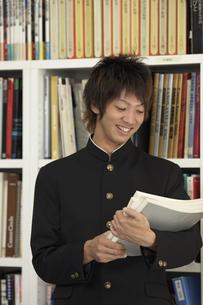 資料を持ち本棚の前に立つ男子学生の写真素材 [FYI03928746]