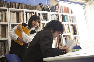 図書室で本を読む男子学生と女子学生の写真素材 [FYI03928770]