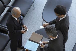 ロビーで名刺を交わしている3人のビジネスマンの写真素材 [FYI03928779]