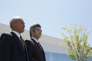 会社の外に立つ2人の男性社員の写真素材 [FYI03928788]