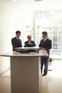 喫煙ルームで話をしている3人のビジネスマンの写真素材 [FYI03928789]
