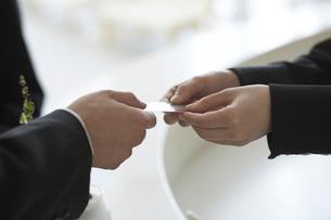 名刺を交わしているビジネスマンと女性の手元の写真素材 [FYI03928790]