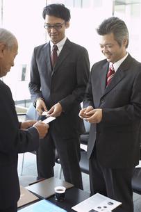 ロビーで名刺交換をする3人のビジネスマンの写真素材 [FYI03928797]