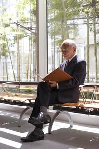 窓ぎわの椅子に座って書類を見るビジネスマンの写真素材 [FYI03928798]