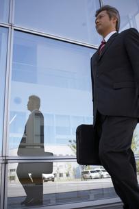 ビルの外を歩くビジネスマンの写真素材 [FYI03928804]