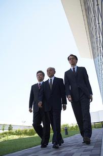 ビルの外を歩く3人のビジネスマンの写真素材 [FYI03928805]
