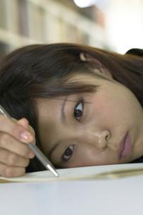 図書室でなまける女子学生の写真素材 [FYI03928811]