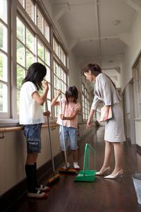 廊下を掃除する生徒と女性教師の写真素材 [FYI03928825]