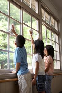 窓ガラスを掃除をする生徒の写真素材 [FYI03928826]