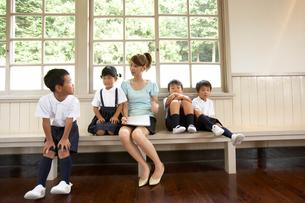 ベンチで話する小学生と女性教師の写真素材 [FYI03928834]