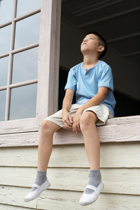 校舎の窓に座る小学生の男の子の写真素材 [FYI03928852]
