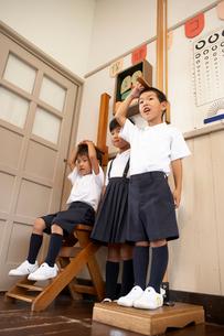 保健室で身長をはかる小学生の写真素材 [FYI03928854]