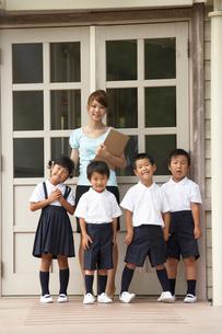 校舎の前に立つ先生と小学生の写真素材 [FYI03928855]