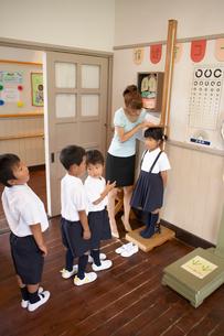 保健室で身長をはかる小学生の写真素材 [FYI03928856]