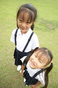 芝生の校庭に立つ小学生の姉妹の写真素材 [FYI03928874]