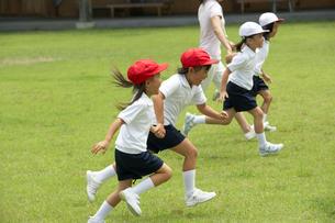 校庭を走る教師と小学生の写真素材 [FYI03928890]