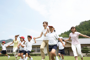 手をつないで走る小学生と教師の写真素材 [FYI03928893]