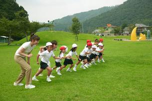 校庭を走る小学生と女性教師の写真素材 [FYI03928894]