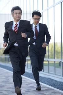 ビルの外を走る2人のビジネスマンの写真素材 [FYI03928916]