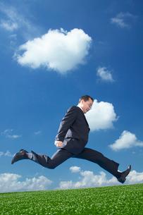 高原でジャンプするサラリーマンの写真素材 [FYI03928960]
