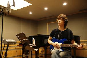 録音スタジオでギターを弾く男性の写真素材 [FYI03929263]