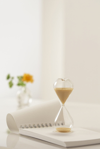 ノートの上に置いた砂時計の写真素材 [FYI03929290]