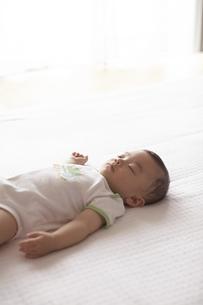 布団の上で寝ている赤ちゃんの写真素材 [FYI03929331]