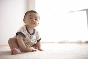 スプーンを持ち座る赤ちゃんの写真素材 [FYI03929343]