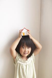 家の模型を頭に乗せ笑顔の女の子の写真素材 [FYI03929392]