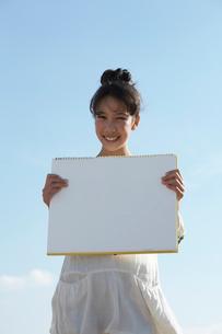 青空と笑顔でホワイトボードを持つ女の子の写真素材 [FYI03929408]
