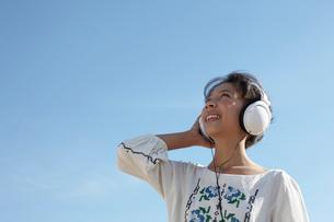 青空とヘッドフォンで音楽を聴いている女の子の写真素材 [FYI03929410]