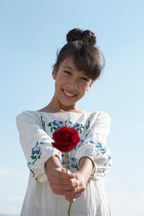 青空と笑顔で赤いバラを差し出す女の子の写真素材 [FYI03929412]