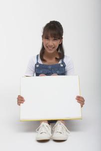 ホワイトボード持って座っている女の子の写真素材 [FYI03929415]