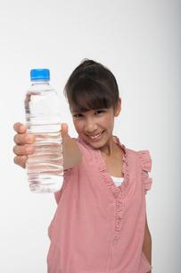 水の入ったペットボトルを差し出す女の子の写真素材 [FYI03929421]