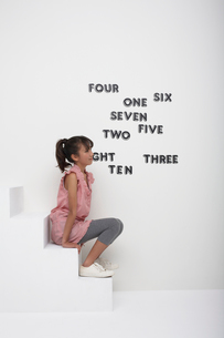 英単語を貼った壁と白い階段に座る女の子の写真素材 [FYI03929426]
