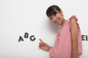 白い壁にアルファベットのシールを指さす笑顔の女の子の写真素材 [FYI03929428]