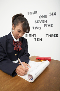 英単語を貼った壁の前の机で勉強をする女子学生の写真素材 [FYI03929435]