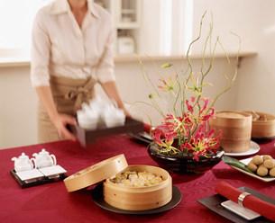 セッティングされたテーブルと女性の写真素材 [FYI03932924]