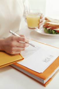 飲食物を手に持ち書いている女性の写真素材 [FYI03933416]