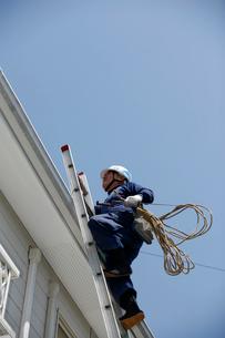 屋根に登る職人の写真素材 [FYI03947894]