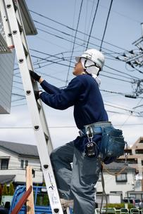屋根に登る職人の写真素材 [FYI03947895]