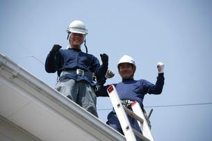 屋根に登る職人の写真素材 [FYI03947897]