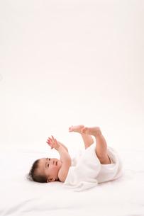 タオルに包まり寝転がる赤ちゃんの写真素材 [FYI03947935]