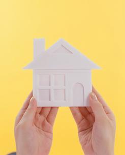 家の形をした物体を持つ手の写真素材 [FYI03947948]
