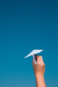 紙飛行機を飛ばそうとしている手の写真素材 [FYI03947963]