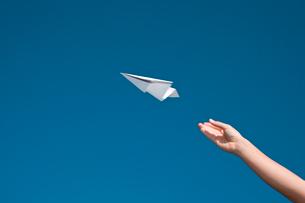 紙飛行機を飛ばす手の写真素材 [FYI03947965]