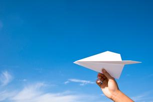 紙飛行機を飛ばそうとしている手の写真素材 [FYI03947967]