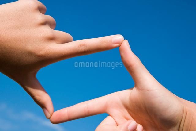 青空バックにフレームを作っている手の写真素材 [FYI03947972]