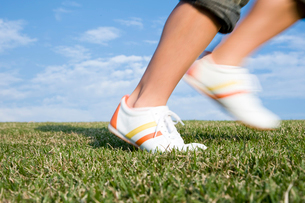 芝生を駆ける足元の写真素材 [FYI03947974]